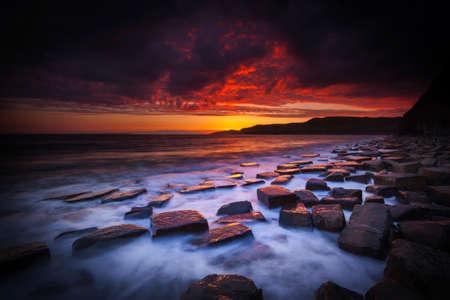 glistening: The sun sets on the beautiful Dorset coastline illuminating glistening rocks with orange and yellow highlights