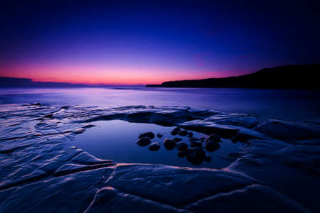 The sun sets on the beautiful Dorset coastline illuminating glistening rocks with orange and yellow highlights photo