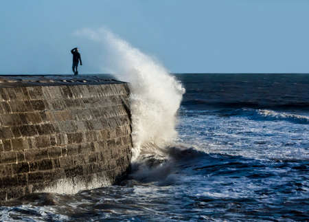 lyme: A lone person braves the elements on a stormy day at the Cobb, Lyme Regis, UK