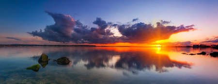 coast line: Rain-bearing clouds hang over the horizon casting reflections in the still waters off the Dorset coastline Stock Photo