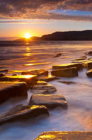 The sun sets on the beautiful Dorset coastline illuminating glistening rocks with orange and yellow highlights Stok Fotoğraf - 33599636