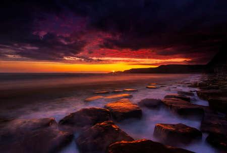 The sun sets on the beautiful Dorset coastline illuminating glistening rocks with orange and yellow highlights