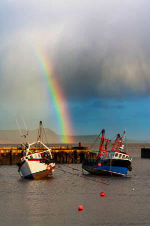 squall: Fishing boats sheltering from the storm in Lyme Regis harbour with a rainbow marking the end of the squall Stock Photo