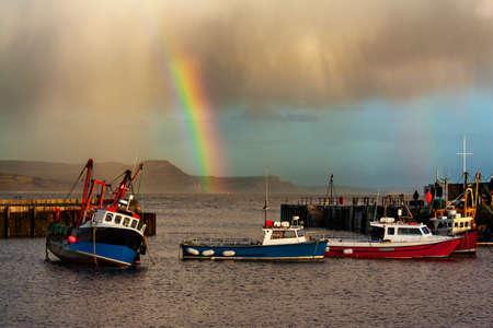 the end of a rainbow: Los barcos de pesca se refugian de la tormenta en el puerto de Lyme Regis con un arco iris que marca el final de la tormenta Foto de archivo