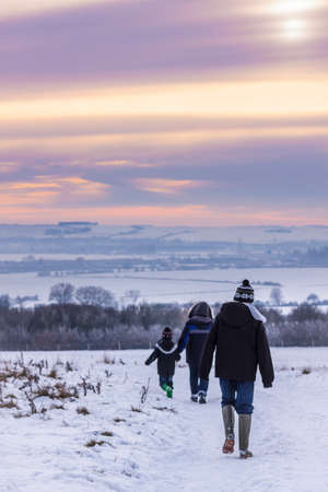 As sunset approaches the mist hangs in valleys over snowy, Oxfordshire fields near Wittenham Clumps. A family walk through the snow towards the sunset.