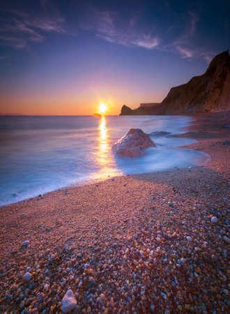 The sun sets illuminating the wet rocks and pebble beaches of the Jurassic Coast