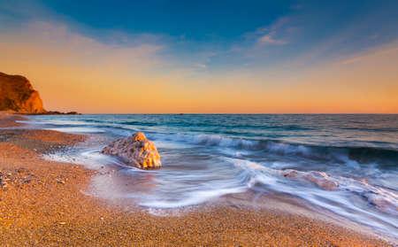 dorset: The sun sets illuminating the wet rocks and pebble beaches of the Jurassic Coast
