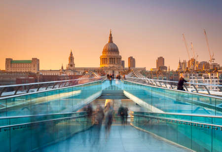 Blurred motion view over the Millennium footbridge looking towards St. Pauls Cathedral at sunset photo