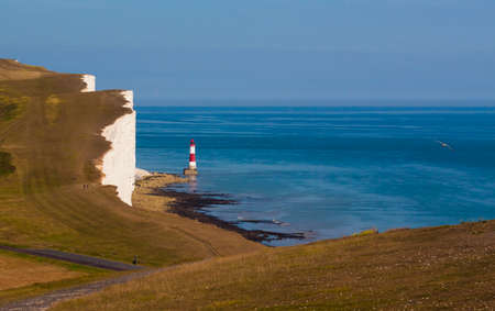 calcium carbonate: Red and white lighthouse on still, blue waters situated at the bottom of white, chalk cliffs