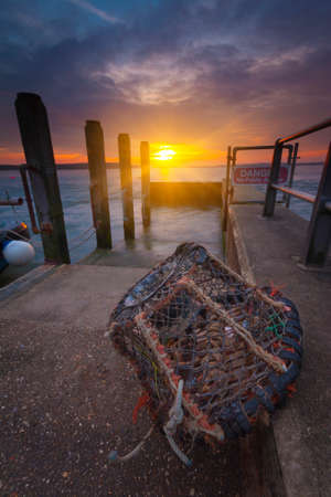 lobster pot: The sun goes down over a lone lobster pot by a slipway