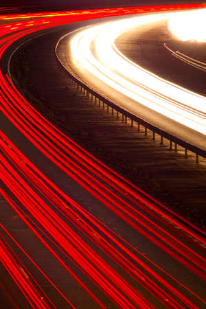 Cars and lorries leave light trails on night road Stock Photo