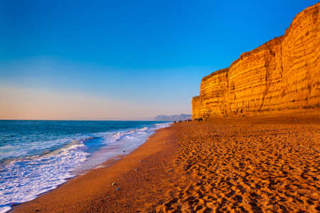Sandstone cliffs tower over golden sandy beaches in Dorset