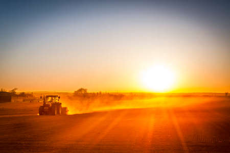 A farmer in a tractor prepares his field as the sun begins to set. The tractor is backlit by the setting sun. The sun is in the upper right corner of the frame, and it is setting behind a low row of hills in the far distance, creating a lens flare photo