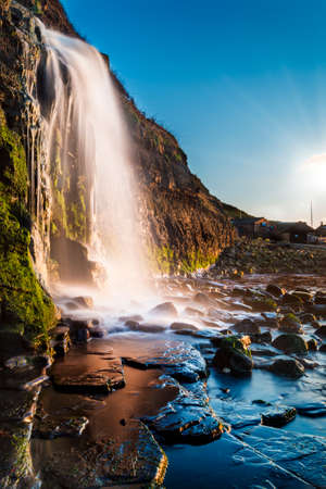 Calm waters at slack tide with a torrential waterfall splashing on the rocks