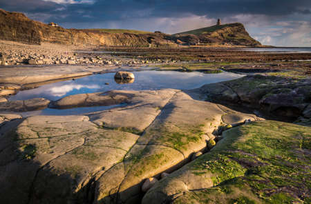 rock strata: Sunlight illuminates the rocks and pools on the craggy Dorset coastline
