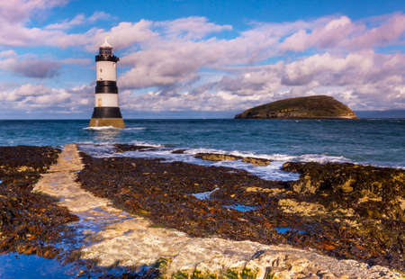 A black and white lighthouse stands tall near puffin island