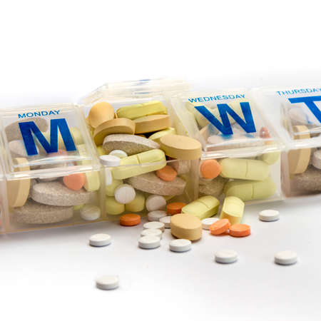 pill box: Pills or supplements spill out of a crammed weekly pill box Stock Photo