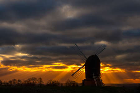 crepuscular: Crepuscular sun rays stream out from behind a silhouetted windmill