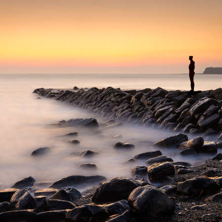 kimmeridge bay: A metal sculpture on a stone jetty overlooks calm waters at Kimmeridge Bay, Dorset Stock Photo