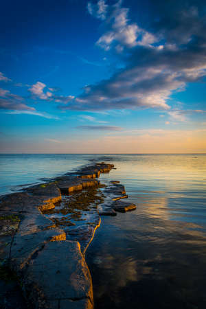 kimmeridge: Clouds are reflected in the calm waters of Kimmeridge Bay at sunset