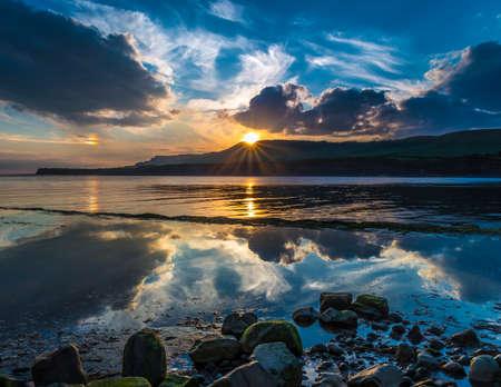 kimmeridge: Golden sunlight illuminates the sea rocks and cliffs on the Jurassic Coastline of South Dorset Stock Photo