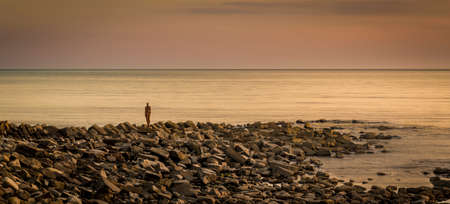 kimmeridge bay: A metal sculpture on a stone jetty overlooks calm waters at Kimmeridge Bay Dorset Stock Photo