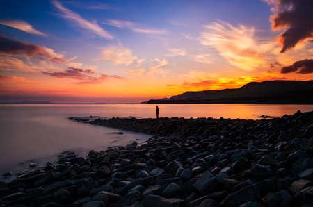 kimmeridge: A metal sculpture on a stone jetty overlooks calm waters at Kimmeridge Bay Dorset Stock Photo