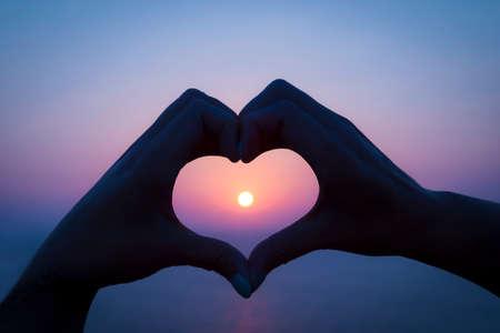 Twee handen maken een hart rond de ondergaande zon op een Grieks eiland vakantie