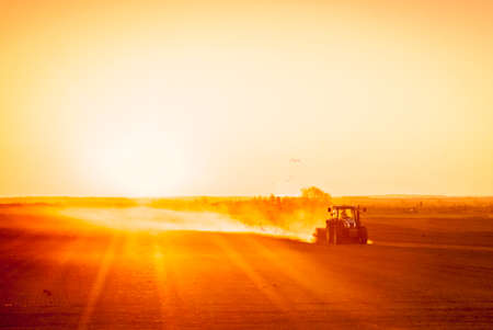 land pollution: A farmer in a tractor prepares his field as the sun begins to set. The tractor is backlit by the setting sun. The sun is in the upper right corner of the frame, and it is setting behind a low row of hills in the far distance. Seagulls flock behind the tra Stock Photo