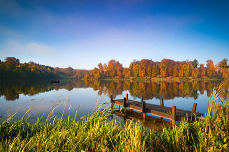 Fishermen doze in a boat on an English lake under autumn sunshine