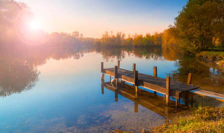 bordering: A wooden jetty juts out onto a calm lake with autumn coloured trees bordering the shores. The sun is setting behind the trees on the far bank