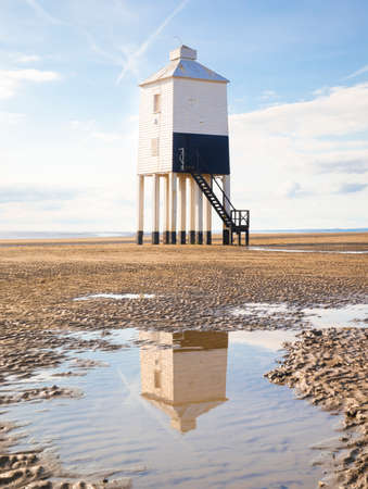 english west country: Wooden lighthouse from 1932 standing tall on stilts at a Somerset beach