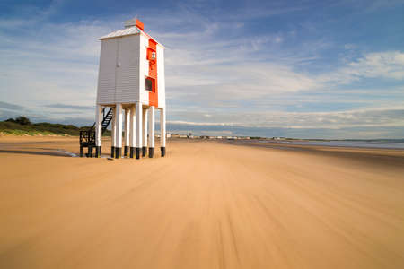 south west england: Wooden lighthouse from 1932 standing tall on stilts at a Somerset beach