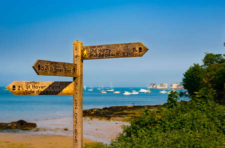 wooden trail sign: Wooden signpost and blue seas