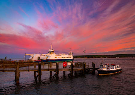 Bournemouth to Swanage Ferry in Poole Harbour under deep red skies Stock Photo