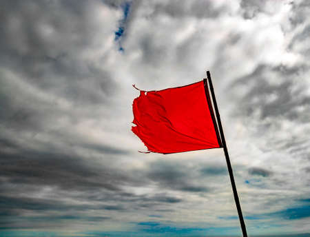 tatty: The wind blows a torn red flag under cloudy skies