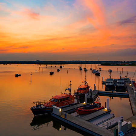 Orange skies over a Dorset harbour with various boats silhouetted on the sea Stock Photo