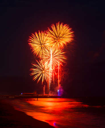 Multi colored Fireworks in the dark blue sky reflected on the wet sand and in the sea at Bournemouth Pier Stock Photo
