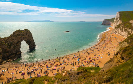Jurassic coastline with bright blue green sea, deep blue skies and yellow sands and cliffs around the Lulworth, Durdle Door, Worbarrow beaches and coves Stock Photo