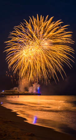 bournemouth: Multi colored Fireworks in the dark blue sky reflected on the wet sand and in the sea at Bournemouth Pier Stock Photo