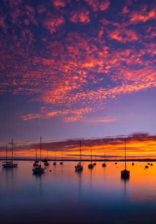 emanate: Deep colours emanate from the sunset, illuminating clouds and the calm seas of Poole Harbour at Rockley