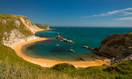 dorset: Jurassic coastline with bright blue green sea, deep blue skies and yellow sands and cliffs around the Lulworth, Durdle Door, Worbarrow beaches and coves Stock Photo