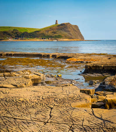Calm waters of Kimmeridge Bay reflect views of Clavells Tower under blue skies Stock Photo