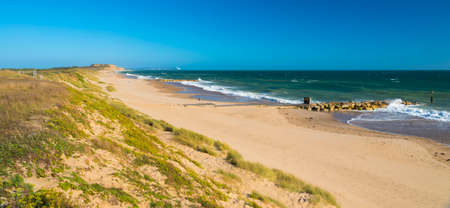 hengistbury: Beautiful pale yellow sands on the Dorset Coast with waves breaking on the shoreline from green seas under blue skies. A fisherman sets up his rod to catch sea bass or bream. Stock Photo