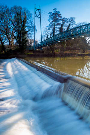 The weir at Blandford crosses the River Stour under a foot bridge Stock Photo