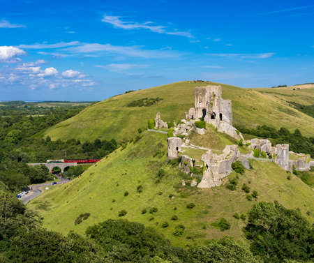 View of Corfe Castle in the Purbeck Hills of Dorset seen from West Hill with vintage train running in the background