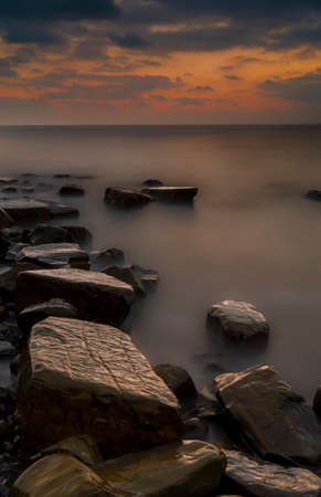 Rocks and rocky ledges of the Jurassic Coast in Dorset illuminated by the afterglow of the sunset