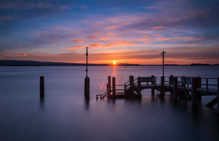 Beatiful rich colourful scene as the sun sets in Poole Harbour around the Sanbanks peninsula Stock Photo