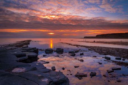 Late evening sun illuminates rocks on the Dorset coastline