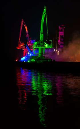 Multi-coloured lights illuminate cranes on the dock side in Poole